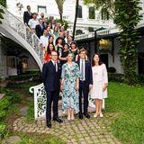 Victoria und Daniel sind zu einem Mittagessen mit einer vietnamesischen Frauenorganisation im Hotel Metropole in Hanoi geladen und posieren mit den anderen Teilnehmern für ein Gruppenfoto im grünen Innenhof.