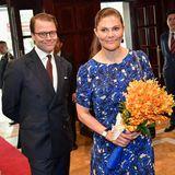 Bei ihrer Ankunft im Hotel Metropole trägt Victoria ein leuchtend blaues florales Kleid.