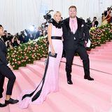 Der britische Moderator James Corden stimmt sich farblich auf seine Frau Julia ab. Während sie eine rosa Robe mit schwarzen Details trägt, wählt er ein rosa Hemd zum schwarzen Smoking.