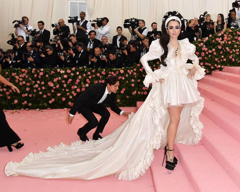 Lily Collins erinnert in ihrem weißen Look von Giambattista Valli Haute Couture ein wenig an die junge Priscilla Presley.
