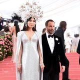 Gemma Chan, hier mitDesigner Tom Ford, sorgt mit ihrem silbernen Göttinnen-Style für ein Blitzlichtgewitter.