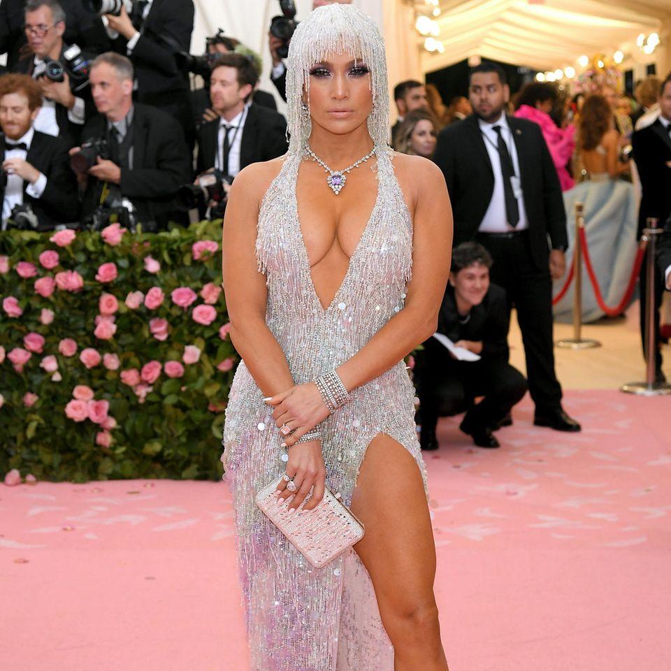 Die Kreation stammt vom amerikanischen Nobel-Juwelier Harry Winston, der eine Halskette mit einem gigantischen, lilafarbenen Saphir umrandet mit runden Brillanten und rautenförmigen Diamanten entwirft. Ein wunderschönes Schmuckstück, das Jennifer Lopez stolz präsentiert!