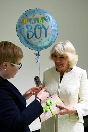 In Berlin wird Herzogin Camilla ein Geschenk und ein Luftballon für Baby Sussex überreicht.
