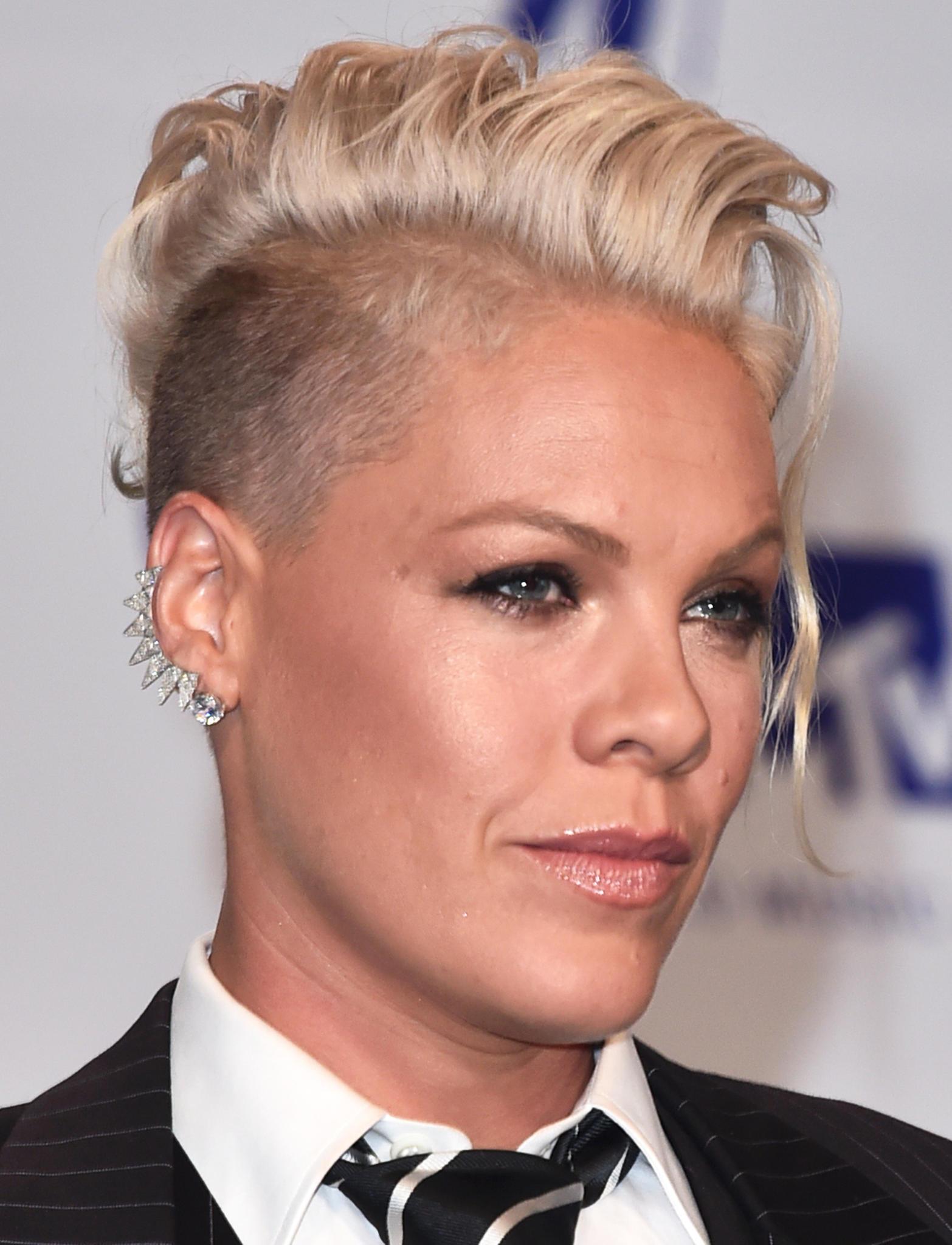 Pink hat ihre Haare auf einer Seite raspelkurz rasiert und trägt auf der anderen blonde Locken. Den punkigen Style betont sie mit einem glitzernden Earcuff.
