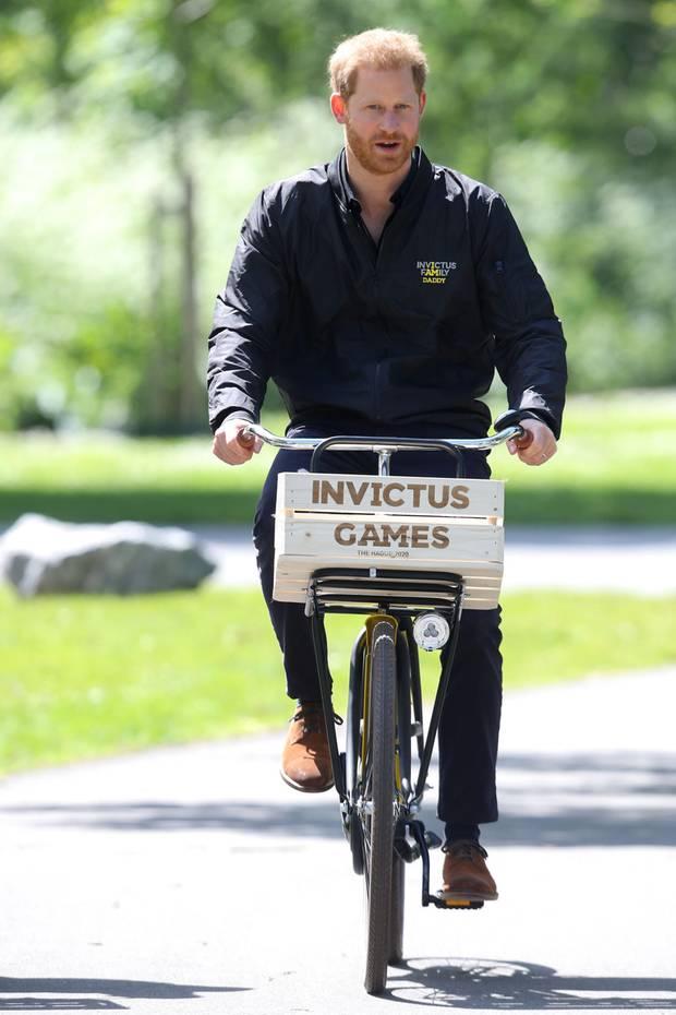 """Prinz Harry macht während seiner Reise nach Den Haag, wo er zum Start der Vorbereitung für die""""Invictus Games"""" zu Besuch ist, auch auf dem Fahrrad eine tolle Figur. Besonderer Hingucker ist jedoch seine Jacke, die enthält nämlich eine kleine Message..."""