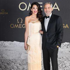 Einfach umwerfend! In Florida präsentiert sich Amal Clooney in einem eleganten Look im Stil der 20er Jahre. Gemeinsam mit ihrem Ehemann George Clooney besucht sie ein Omega-Event anlässlich der Mondlandung, die sich zum 50. Mal jährt. Dabei trägt die Juristin ein glänzendes Fransen-Kleid, das stark an die Zeiten des Wirtschaftsaufschwungs erinnert.