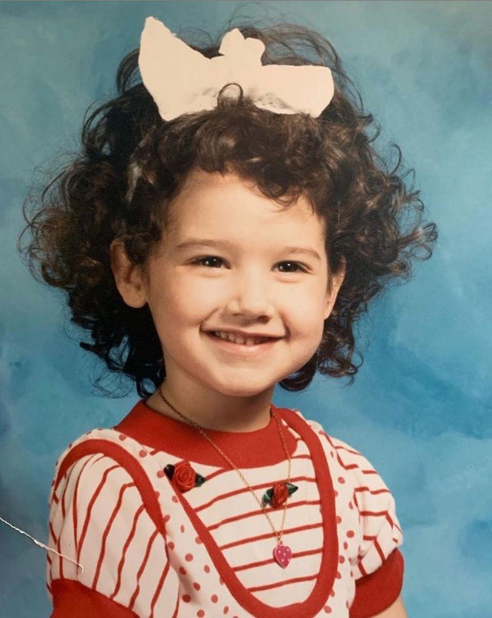 Ashley Tisdale  Wie niedlich! Mit dunklen Locken und einer großen Schleife im Haar lächelt Ashley Tisdale verschmitzt in die Kamera. Für das Fotoshooting in der Schule hat sie sich extra schick gemacht: Das verspielte Oberteil warihr absolutes Lieblingskleiderstück, wie sie ihren Fans auf Instagram verrät.