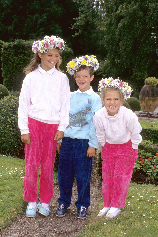 Victoria, Carl Philip und Madeleine lachen mit Blumenkränzen im Haar in die Kamera.