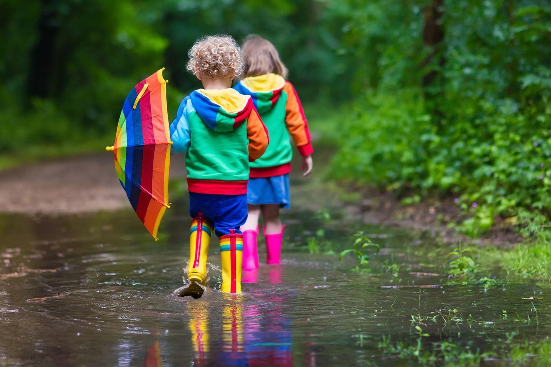 Kinder spielen in einer Pfütze