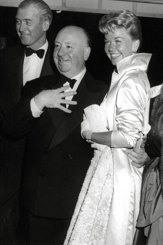 """Zusammen mit James Stewart (l.) steht Doris Day 1956 für den Streifen """"Der Mann, der zu viel wusste"""" von Regisseur Alfred Hitchcock (M.) vor der Kamera."""