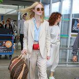 Elle Fanning zieht in einem beigen Anzug alle Blicke auf sich. Luxus-Accessoires von Chanel und Louis Vuitton runden ihren schicken Look ab.