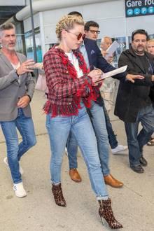 Bei ihrer Ankunft am Flughafen von Nizza stellt Amber Heard ihre Multitasking-Künste unter Beweis. Laufend schreibt sie Autogramme für Fans, ein Bodyguard passt auf, dass sie dabei nicht gestört wird. Sie setzt auf hohe Boots, Jeans und ein schickes, rotes Jäckchen.