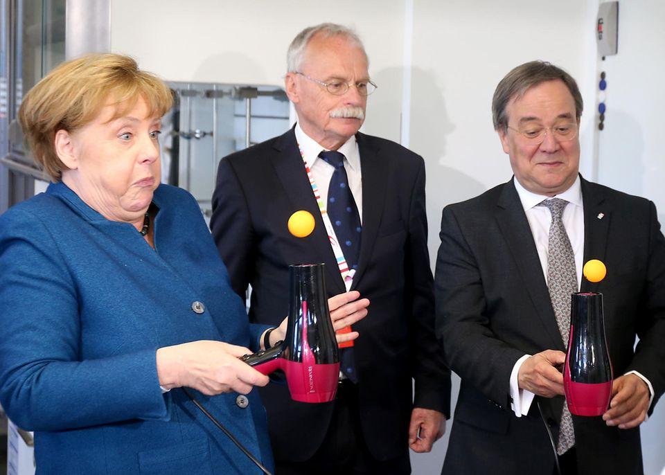 Hier ist Konzentration angesagt: Bundeskanzlerin Angela Merkel,NRW-MinisterpräsidentArmin Laschet (links) und der Gründer der Junior Universität in Wuppertal Ernst-Andreas Ziegler (mitte)versuchen,einen Tischtennisball auf einem Föhn zujonglieren.