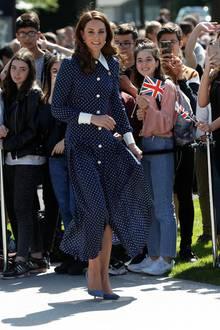 """Für denBesuch einer Ausstellungin """"Betchley Park"""" trägt Herzogin Catherine ein dunkelblaues Kleid mit weißen Punkten und spitzem Bubikragen. Das Kleid trug sie zuletzt auf den offiziellen Geburtstagsportraits von Prinz Charles."""