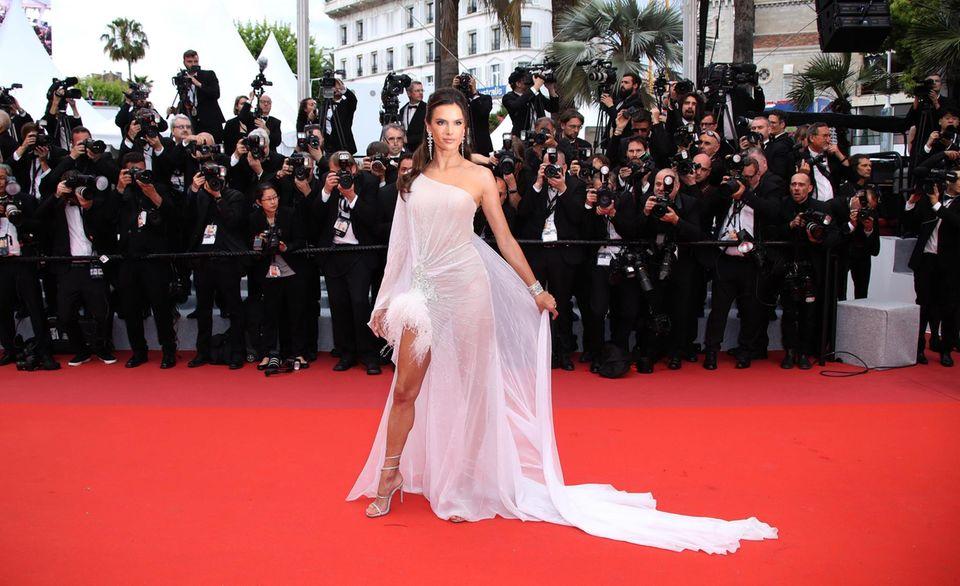 Model Alessandra Ambrosioträgt ein weißes Chiffonkleid mit einem gewagten Schlitz und einem gefiederten Saum.