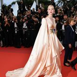 Diese Robe ist dem roten Teppich von Cannes mehr als würdig: Schauspielerin Elle Fanning sieht hat sich für ihren großen Auftritt für ein extravagantespfirsichfarbenesKleid mit langen Cape-Armenentschieden.In FanningsKörpermitte zieht eine lilafarbene Stoffblume mit grüner Blatt-Applikation die Blicke auf sich.