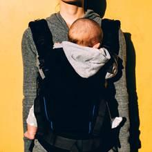Eine Mutter trägt ihr Kind in einer Trage (Symbolbild).