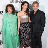 """Strahlender, als jedes Accessoire: George Clooney erscheint mit seiner Ehefrau Amal und ihrer MutterBaria Alamuddin zur London-Premiere seines Films """"Catch-22"""". In einem fließenden türkisen Look zieht Baria alle Blicke auf sich."""