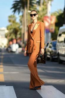 Vor allem die quadratische Tasche von Stefanie Giesinger fällt ins Auge. Unter ihrem Hosenanzug trägt sie nichts außer einem schwarzen BH.