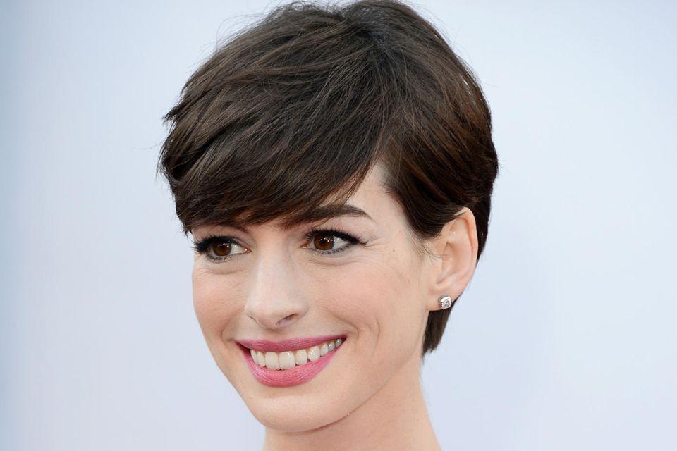 Anne Hathaway trägt den Pixie-Cut mit einem langen Pony und elegantem Seitenscheitel.