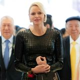 """Charlènevon Monaco trägt ein schwarzes, hautenges Kleid in einem Krokodil-Leder-Print von Tom Ford für 1.750 Euro. Dazu kombiniert sie eine Handtasche von Louis Vuitton - das Modell """"BB Capucines"""" in einer Sonderedition (das Modell ist ab 3.400 Euro zu haben)."""