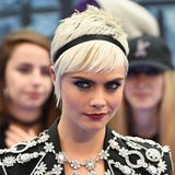 Model Cara Delevingne trägt einen platinblonden Pixie-Cut.