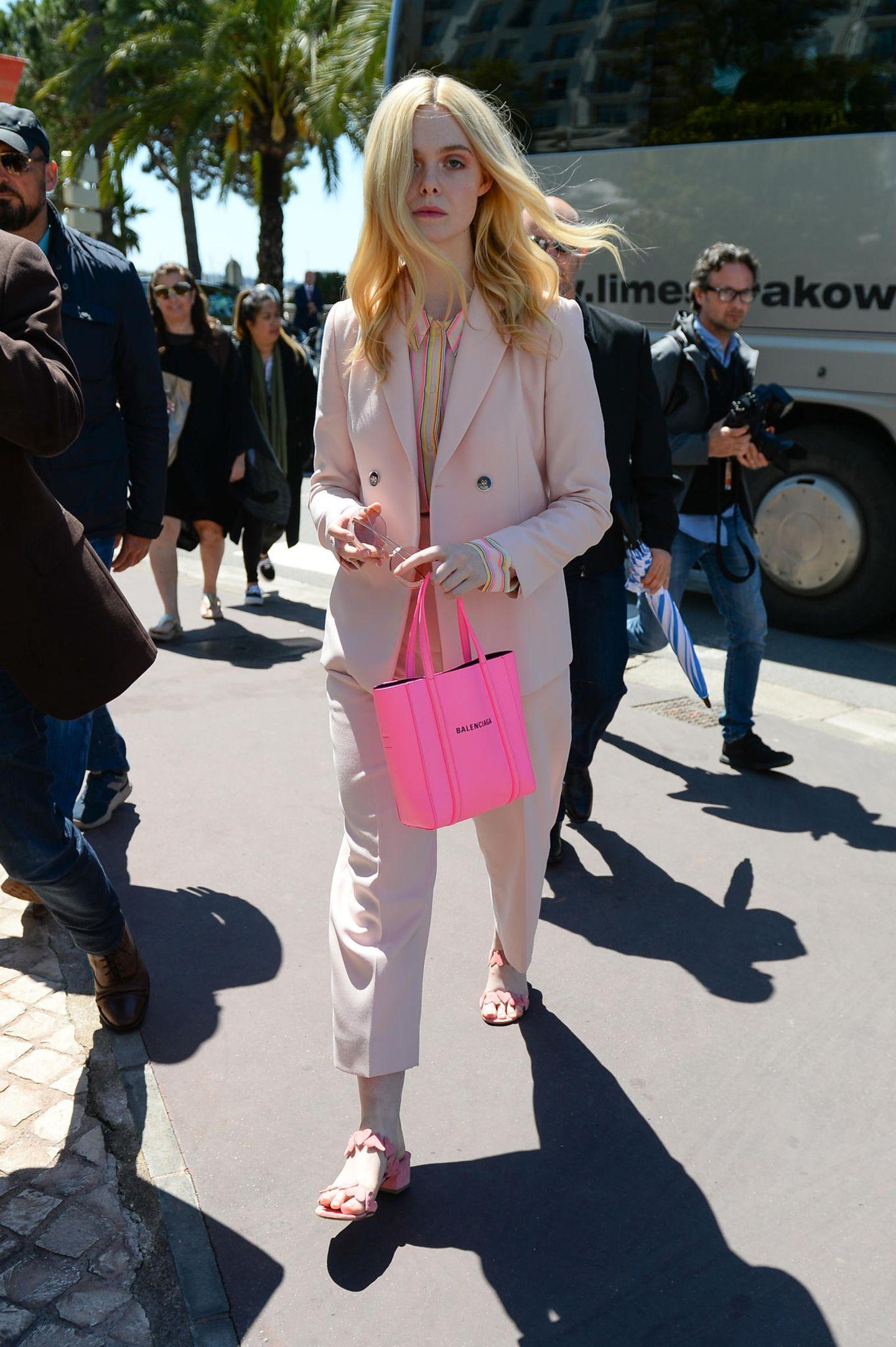 Bevor es zum Fotoshooting mitL'Oréal geht, spaziert Elle Fanning, diesjähriges Jurymitglied der Filmfestspiele, in einem rosafarbenen Hosenanzug und pinkfarbener Handtasche durch Cannes.