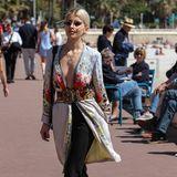Influencerin Caro Daur zieht mit ihrem extravaganten Outfit auf den Straßen von Cannes alle Blicke auf sich. Die Hamburgerin trägt eine weit ausgeschnittene florale Bluse, die ein großer Gürtel in der Taille zusammenhält.