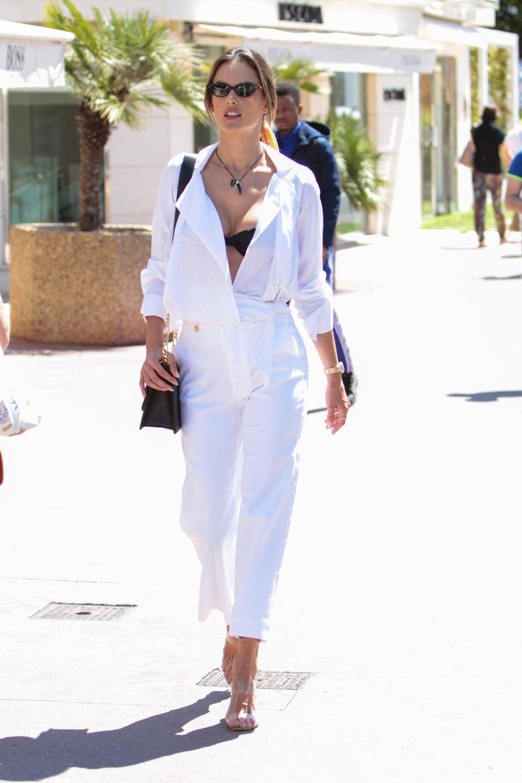 Alessandra Ambrosio stimmt ihr Outfit perfekt auf den edlen Ort anderCôte d'Azurab und wählt für einen entspannten Spaziergang einen weißen Sommerlook mit sexy Ausschnitt.