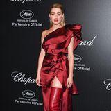 Amber Heard erscheint als Lady in Red zur Party von Chopard. Sie trägt ein aufwendig drapiertes Kleid von Elie Saab und auffällige Overknee-Stiefel.