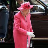 In einem pinkfarbenen Mantel und dem farblich passenden Hut, erscheint die Queen Elizabeth bei der Hochzeitsgesellschaft.