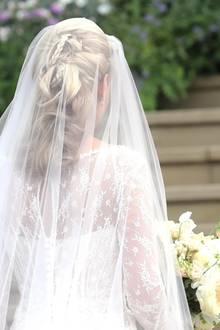 Ihr blondes Haar trägt sie halb hochgesteckt; kunstvoll drapierte Flechtzöpfe und Locken lenken den Blick auf die Spitze und die kleinen Knöpfe, die die Rückseite des Kleides zieren.