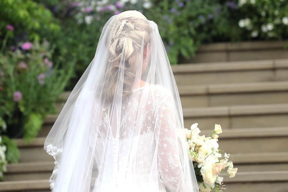 Das kunstvoll hochgesteckte Haar von Lady Gabriella legt sich auf den Spitzenbody, der von filigranen Knöpfen zusammengehalten wird.