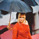 """Vor dem Regen gut geschützt, wird Iskra Lawrence zur Vorführung des Films """"Les Plus Belles Annees D'Une Vie"""" geleitet."""