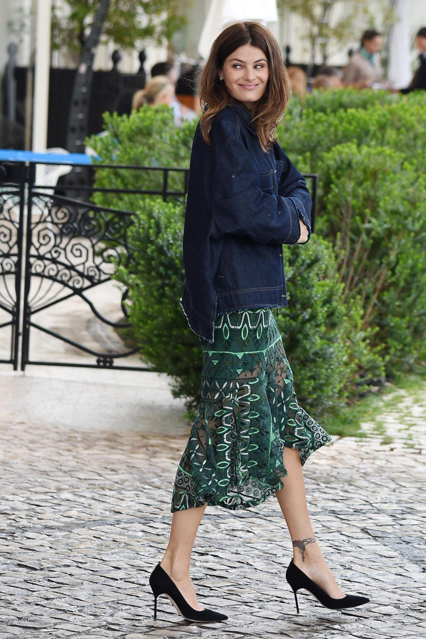 Isabeli Fontana hüllt sich in eine dunkelblaue Jeansjacke. Scheint, als sei ihr das grün-gemusterte Kleidchen, das sie darunter trägt, zu kalt.