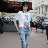 """Coco Rocha setzt auf eine Jeans mit coolen Schleifendetails und ein bedrucktes Shirt aus der """"SupremexGaultier""""-Kollektion. Rote Lippen, derbe Boots und eine schwarze Schiebermütze geben dem Styling das gewisse Etwas."""