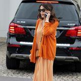 Iris Berben führt ein Telefonat auf der Straße. Sie trägt ein orange-kariertes Blusenkleid mit farblich abgestimmten Cardigan. Beige Accessoires machen den Look perfekt.