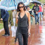 Lena Meyer-Landrut macht die verregneten Straßen Cannes' zu ihrem Laufsteg: Zu ihrem schwarzen Outfit und der XL-Sonnenbrille setzt sie mit einem blau-weiß gestreiften Schirm einen farblichen Akzent.