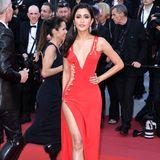 25 Jahre später trägtPraya Lundberg auf dem roten Teppich in Cannes ein fast identisches Modell von Atelier Versace. Mit hohem Beinschlitz, den berühmten Sicherheitsnadeln und in Knallrot macht auch die Schauspielerin eine tolle Figur.