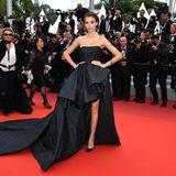 Josephine Skriver hat ein schwarzes Vokuhila-Kleid gewählt, das ihre Taille wundervoll betont.