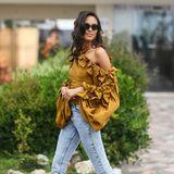 Zu einer einfachen Jeans kombiniert Cindy Bruna eine auffällige Bluse mit One-Shoulder-Schnitt und vielen Schleifen, sodass ein toller Style entsteht.