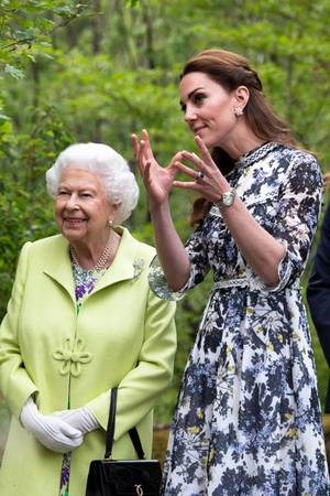 """Catherine erklärt der Großmutter ihres Mannes ihr Herzensprojekt - ihren """"Zurück zur Natur""""-Garten. Dabei wird die Schuhwahl der Herzogin ganz bestimmt zur Nebensache. Witziges Detail: Kurz bevor die Queen kam, räumte Kate ihren Garten noch einmal auf und ließ herumfliegende Blätter in ihrer Designerhandtasche verstecken."""
