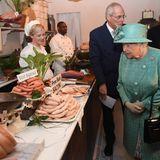 So sehen Supermarktketten heute nicht mehr aus. Queen Elizabeth begutachtet trotzdem interessiert die Lebensmittelauswahl, dieLord Sainsbury und seine Ehefrau für den hohen Besuch ausgewählt haben.