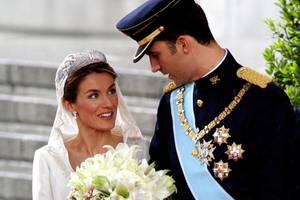 """Königin Letizias """"Schneewittchenkleid"""" mit kurzem Kragen wird von Designer Manuel Pertegaz entworfen und steht der Frau von König Felipe ausgezeichnet! Zu ihrem Brautkleid trägt sie eine funkelnde Tiara und ebenso funkelnde Ohrringe."""