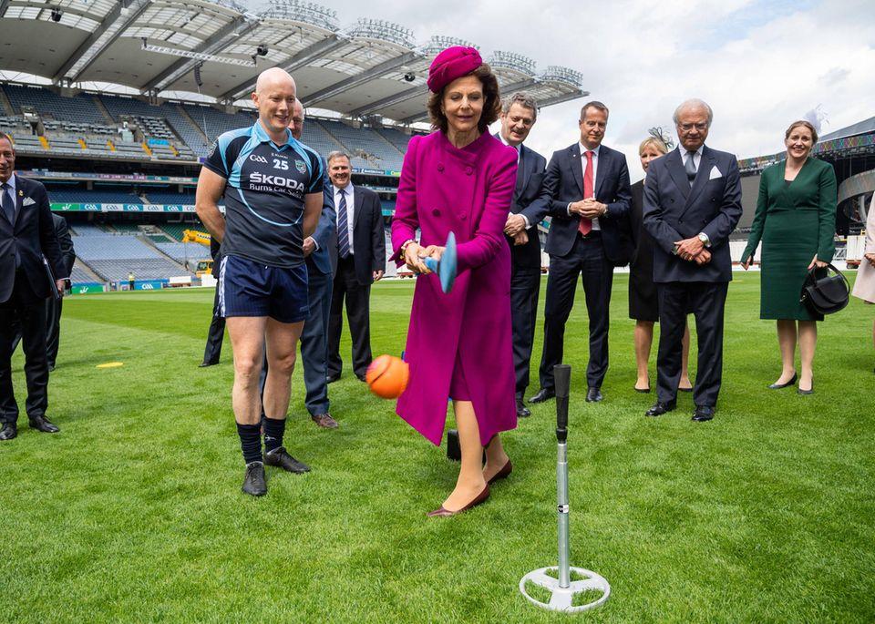 Mit Schwung, Eure Majestät! Königin Silvia probiert es am ersten Tag ihres Staatsbesuchs in Irland gleich mal mit Hurling, einer der rasantesten Mannschaftssportarten der Welt.