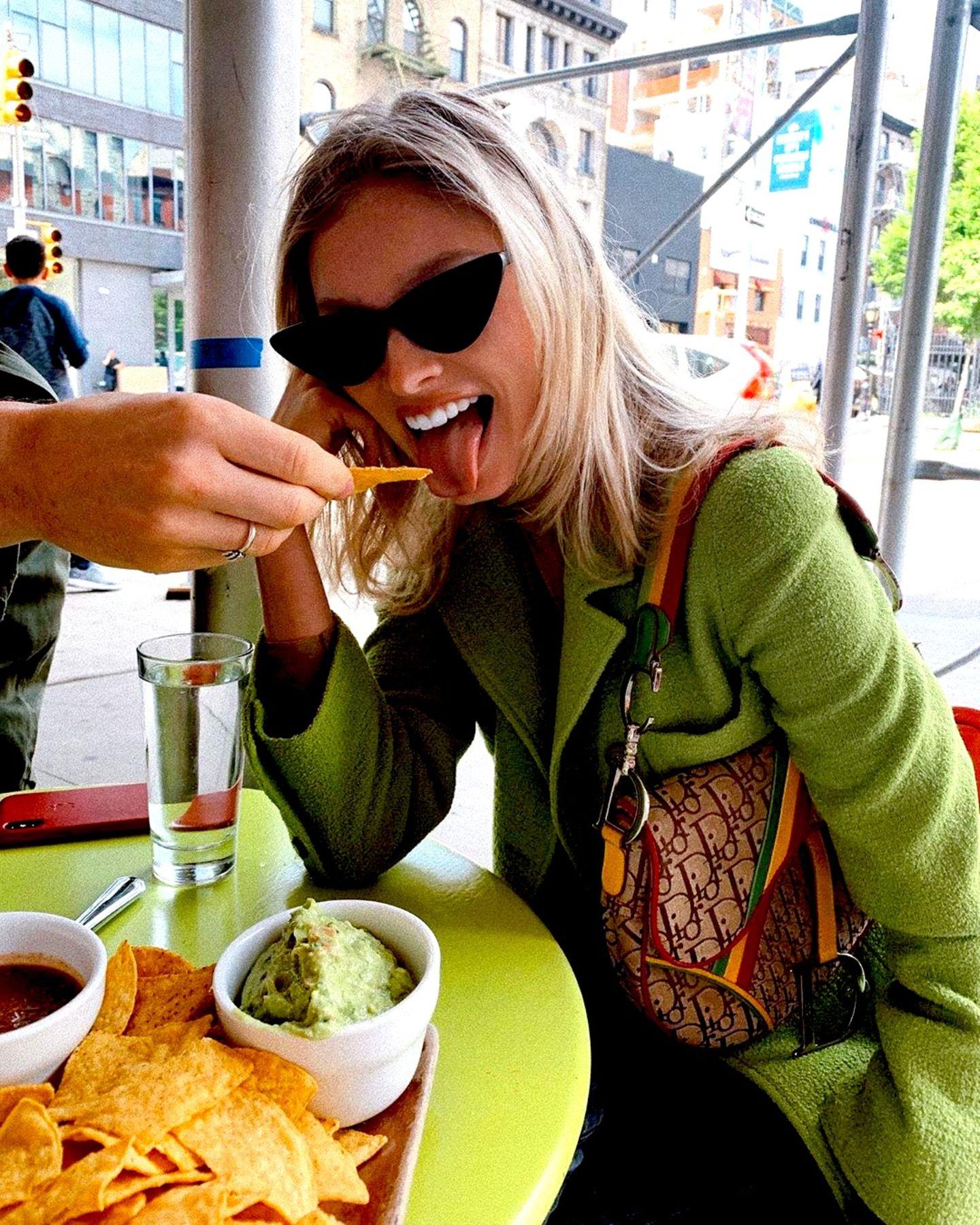 Farblich passend zur Guacamole vor ihr auf dem Tisch trägt Elsa Hosk ein grünes Jackett, als sie sich knusprige Tacos gönnt. Auf einem Tablett serviert, findet sich außerdem noch ein feuriger Salsa-Dip neben der grünen Variante. Das Beste: Die 30-Jährige muss sich nicht einmal die Finger schmutzig machen, sondern wird von ihrer Begleitung gefüttert – wie lieb!