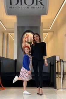"""Posieren wie eine Große kann Harper Beckham schon: Frech hebt sie ihr rechtes Bein in die Luft und neigt ihren Kopf zur Seite als das Foto geschossen wird. In einem gemusterten Kleid und einem roten Haarband – übrigens das ultimative It-Piece des Sommers und Blair Waldorfs liebstes Accessoire – sieht die 7-Jährige einfach zuckersüß aus! Mama Victoria Beckham mag es an diesem Tag nicht sonderlich farbenfroh und wählt ein schwarzes Outfit. Gemeinsam besucht das Mutter-Tochter-Duo das """"Victoria andAlbert Museum"""" in London."""