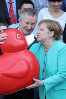 23. Mai 2019  Angela Merkel bekommt zumAbschluss ihres Besuches der Biotech-Firma Centogene von Vorstandsvorsitzenden Arndt Rolfseine große rote Ente geschenkt, das Maskottchen der Firma. Die Freude über das außergewöhnliche Geschenk scheint groß zu sein: Die Bundeskanzlerin deutet einen dicken Schmatzer für die Ente an.