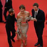 So einfach scheint es gar nicht zu sein, in einem Couturekleid die Stufen vor dem Filmpalast zu erklimmen. Milla Jovovich braucht gleich zwei Helfer.