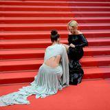 Weniger schwungvoll geht es währenddessen bei Virginie Efira zu, die mit dem Verschluss ihrer High-Heels kämpft. Zusammen mit Schauspielkollegin Adele Exarchopoulos versucht sie das Problem auf der Treppe zum Filmpalast zu fixen.